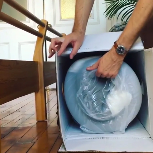 Man opening a Cocoon™ by Sealy Box with his mattress inside